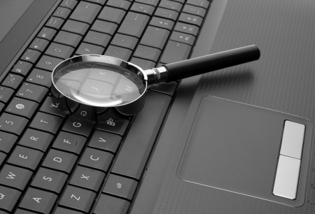 Magnifying glass on laptop computer keyboard Stock Photo - 18314211