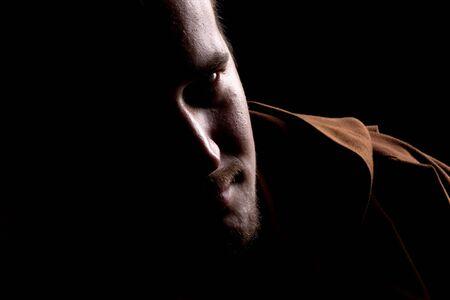 sotana: Retrato del monje pensativo en la oscuridad