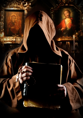 Portrait of medieval monk with bible in church