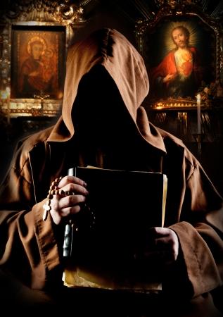 sotana: Retrato del monje medieval con la biblia en la iglesia