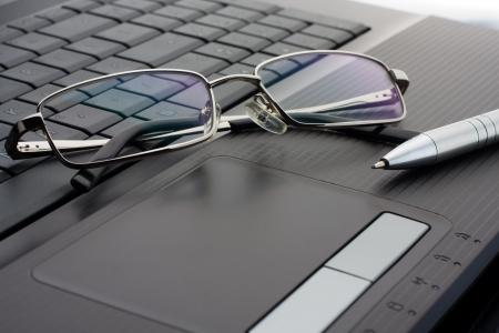 articulos oficina: Empresario de gafas y la pluma en el ordenador portátil