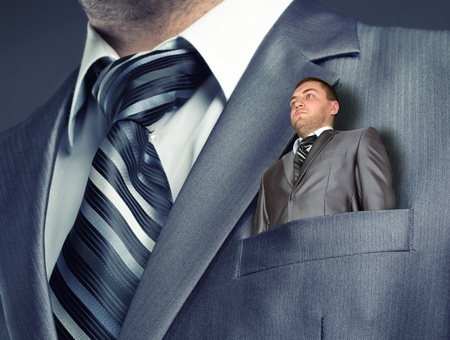 Small puppet businessman in suit pocket Stock Photo - 18348803
