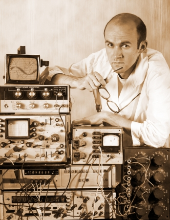 Portrait of pensive scientist at vintage technological laboratory. Sepia toned photo