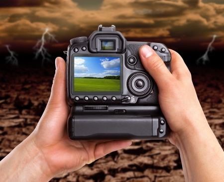 Hands holding digital camera and capturing beautiful landscape against dramatic area photo