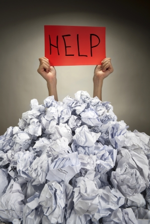 Hands with red frame reaches out from big heap of crumpled papers Stock Photo - 18363437
