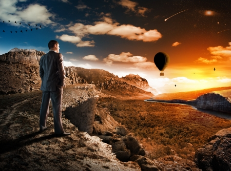 Businessman in mountains looking at sunset Stock Photo - 18359208