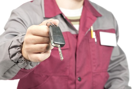 Close-up of mechanic giving a car key. Isolated on white Stock Photo - 18358972