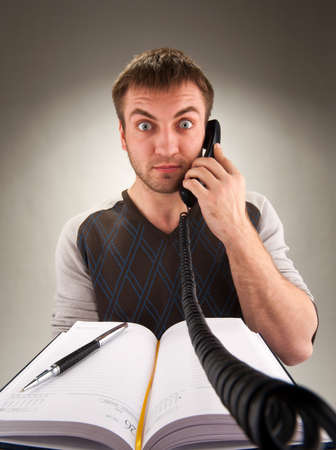 shoked: Portrait of surprised office manager talking by phone