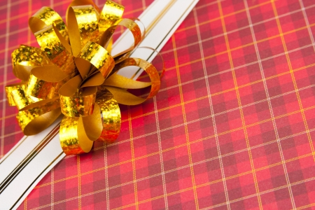 Gold ribbon and bow on red gift paper photo