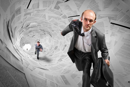 Serious businessmen running inside big documents tunnel Stock Photo