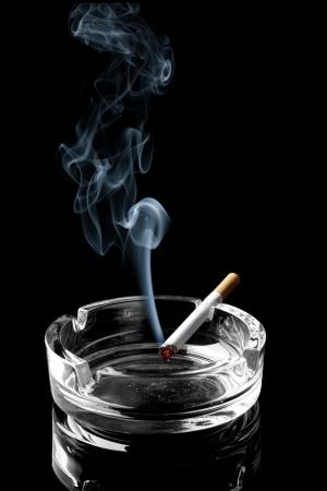wisp: Close-up van sigaret op asbak met sliert van rook Stockfoto
