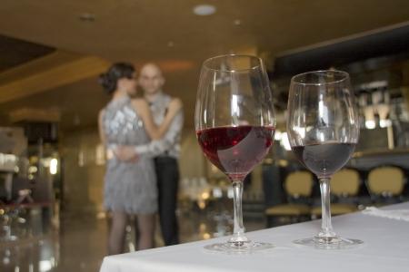 Copas de vino sobre la mesa con la pareja de baile en el fondo