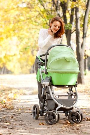 Madre joven feliz que lleva el beb� en oto�o parque