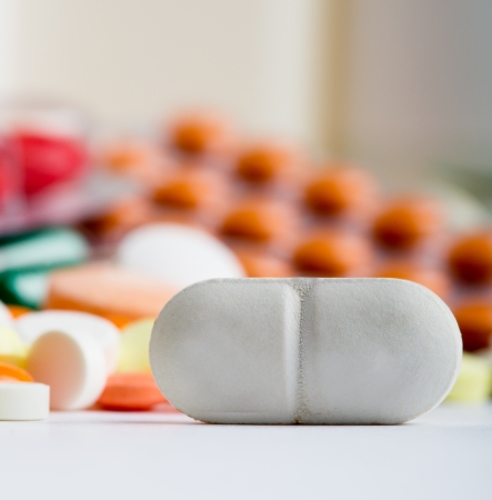 pills bottle: Closeup of white pill with various medicines on background