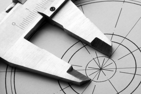Close-up of engineering drawing and caliper