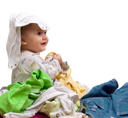 babys: Happy baby girl playing in heap of babys wear. Isolated