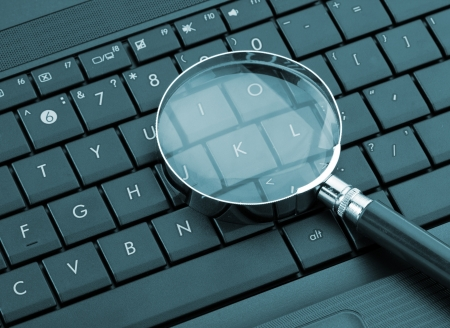 Magnifying glass on laptop computer. Toned in blue Stock Photo - 18365511