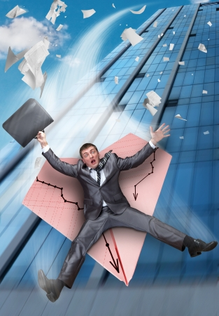 Scared businessman on paper airplane falling from business building photo