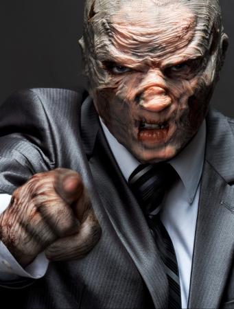 jefe enojado: Monstruo enojado en traje de negocios apuntando a usted