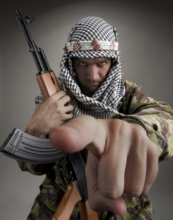 Serious middle eastern man with AK-47 pointing to you photo