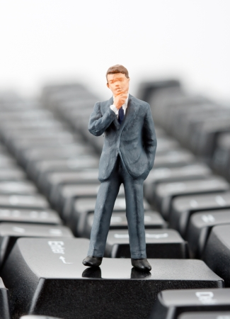 Miniature figurine of successful businessman standing on computer keyboard photo