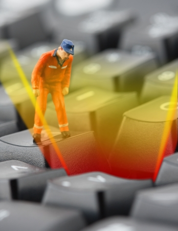 Figurine of worker looking into pit in computer keyboard Stock Photo - 18396874