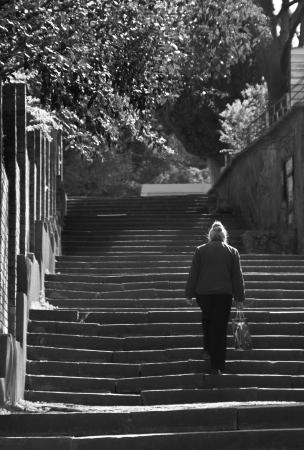 upstairs: Old woman walks upstairs. BW