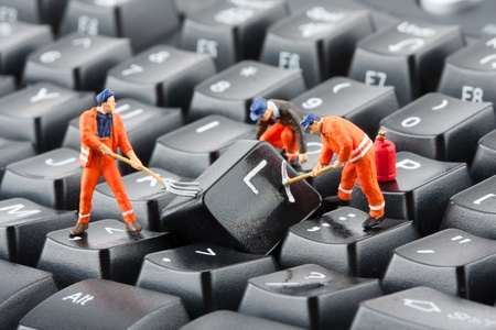 repair computer: Small figurines of workers repairing computer keyboard Stock Photo