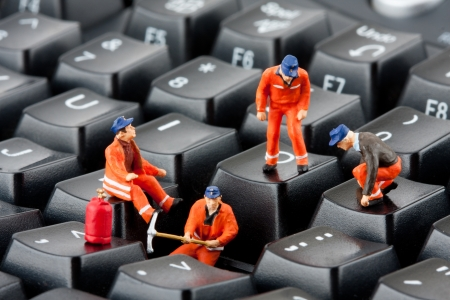 computer key: Small figurines of workers repairing computer keyboard Stock Photo