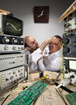 Scientific conflict. Two funny nerd scientists fighting at vintage laboratory photo