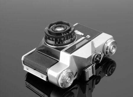 dslr camera: Old photographic camera on gray reflective surface