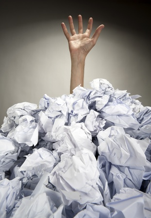 office chaos: Hand reaches out from big heap of crumpled papers Stock Photo