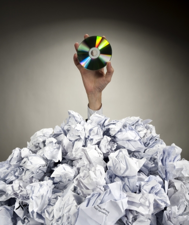 finance a helping hand confusion: Hand with CD reaches out from big heap of crumpled papers Stock Photo