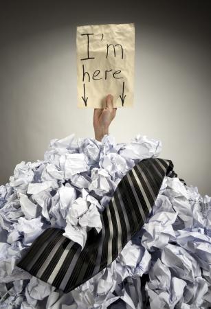 Empresario enterrado en el montón grande de papeles arrugados