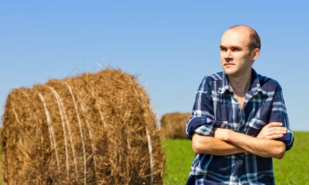 Morning portrait of farmer in field against wheat bales photo