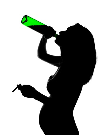 drinking problem: Silhouette of careless pregnant woman with alcohol and cigarette Stock Photo