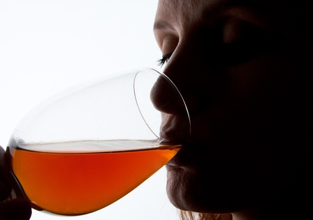 Silhouette of woman degusting wine. Close-up portrait photo