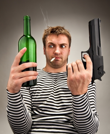 Drunk bizarre sailor choosing between bottle and gun photo