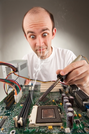Bizarre electronics repairing computer circuits by soldering pen Stock Photo - 18398274
