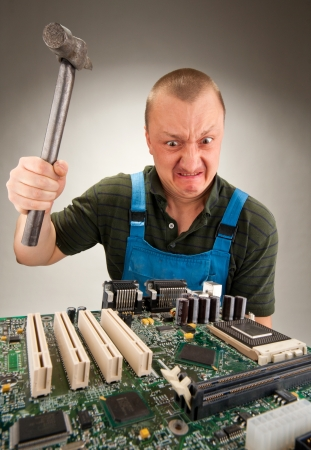 Mad IT worker repairing computer circuits by hammer photo