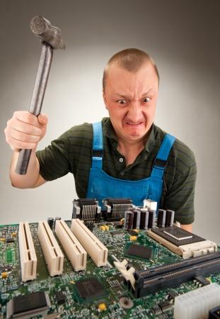 Mad IT-werknemer repareren van computer circuits door hamer