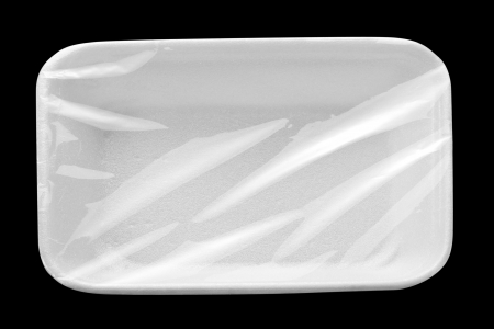 Empty wrapped white food tray. Isolated on black photo