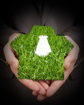 Businessman holding green grass suit in hands Stock Photo - 18397449