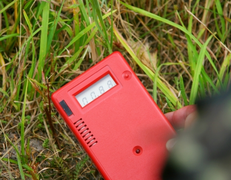 emissions: Worker measuring environmental radiation level by dosimeter