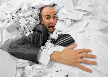 office chaos: Businessman sinking in heap of documents and asking for help