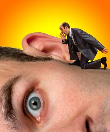 big ear: Small businessman screaming to big man ear Stock Photo