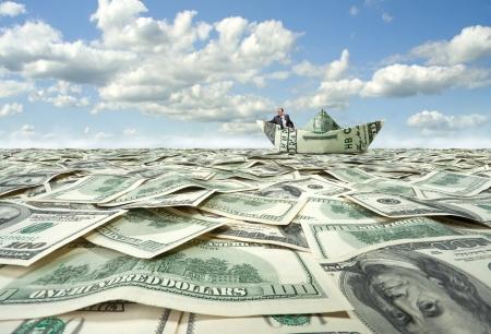Succesvolle zakenman zeilen op dollar boot in financiële zee Stockfoto