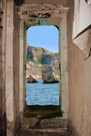 bow window: Shipwreck. Rusty abandoned cargo ship near mountain coast