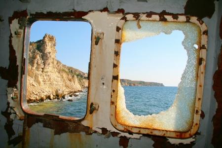 bow window: Shipwreck. Rusty abandoned cargo ship near mountain coast. Broken window