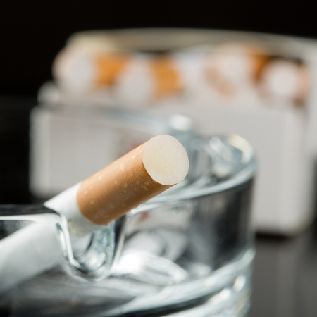 Closeup of cigarette on ashtray with pack on background photo